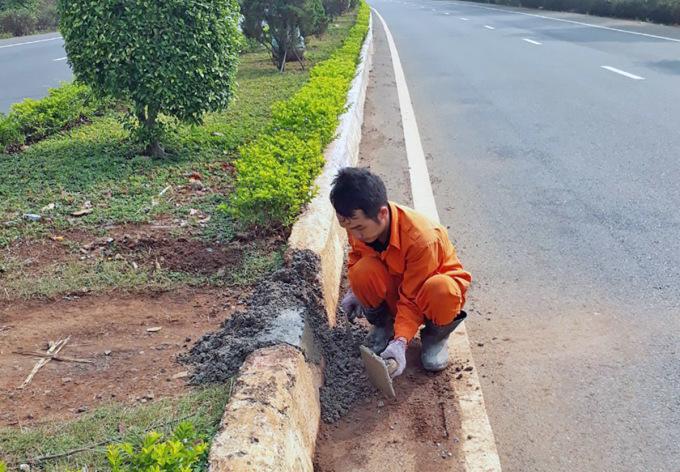 Nhân viên quản lý tuyến cao tốc xây lại con lươn bị người dân phá để xe máy đi ngang đường. ẢNH: Khánh Hương