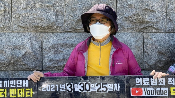 Lee Na Geum cầm biểu ngữ đứng trước tòa quốc hội để yêu cầu thắt chặt luật xử lý bác sĩ ma. Ảnh: CNN.