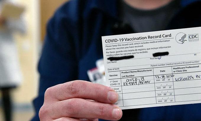 Một nhân viên y tế bệnh viện Bệnh viện Poudre Valley ở Colorado, Mỹ, cầm trên tay giấy chứng nhận tiêm chủng vaccine Pfizer. Ảnh: Denver Post.