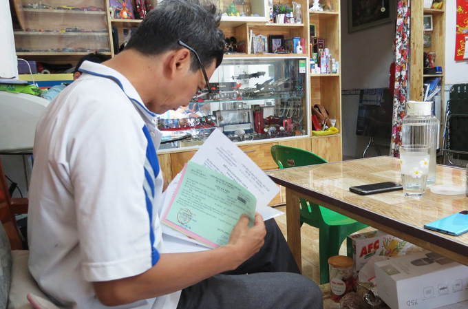 Thầy giáo Nguyễn Văn Hoành xem hồ sơ đề nghị nhận bảo hiểm xã hội một lần, ngày 13/4. Ảnh: Lê Tuyết.