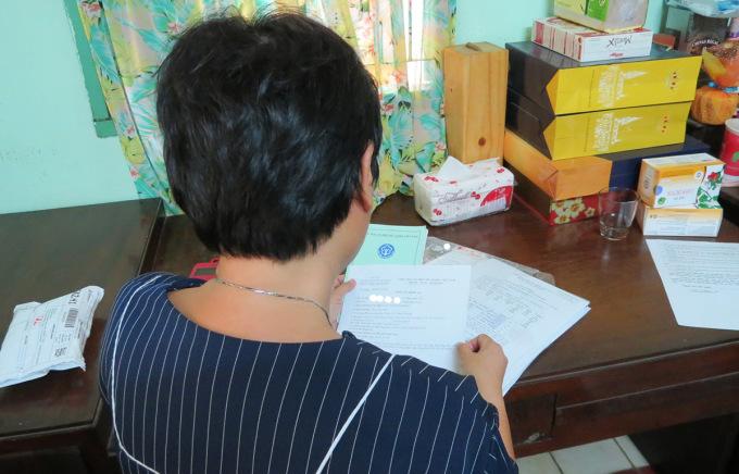 Bà Nguyễn Chi Hồng xem hồ sơ bệnh án của mình và chồng, ngày 11/4.  Ảnh: Lê Tuyết.