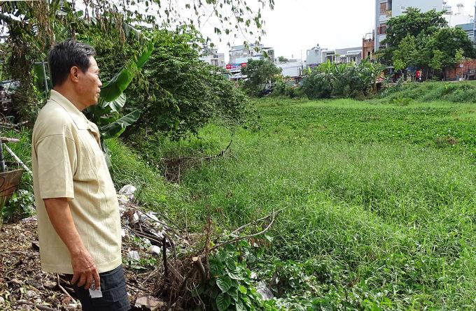 Ông Lân đứng bên kênh Tham Lương đầy cỏ dại, lục bình và rác thải. Ảnh: Hà An.