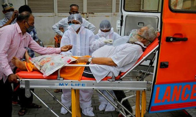 Một bệnh nhân Covid-19 thở oxy được đưa khỏi xe cấp cứu ở thành phố Ahmedabad, bang Gujarat hôm 26/4. Ảnh: Reuters.