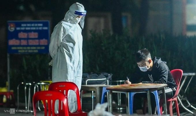 Lực lượng y tế làm việc với các F1 ở huyện Đông Anh để đưa đi cách ly rạng sáng 30/4. Ảnhh: Giang Huy