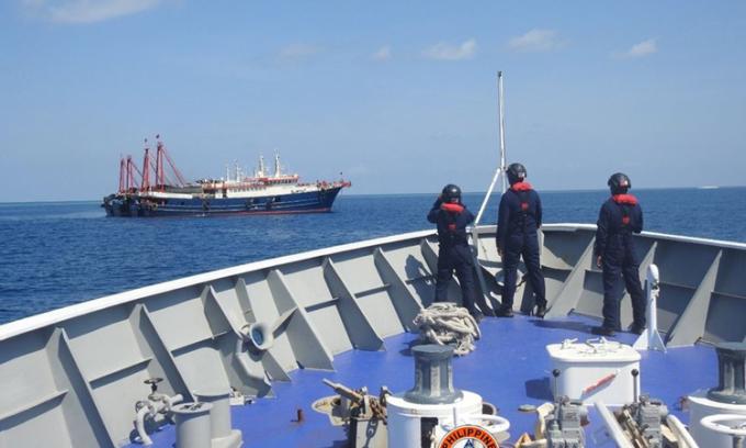Cảnh sát biển Philippines quan sát một số tàu được cho là của lực lượng dân quân Trung Quốc ở bãi Sa Bin,  thuộc quần đảo Trường Sa của Việt Nam hôm 27/4. Ảnh: Reuters.