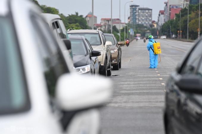 Nhân viên y tế khử khuẩn đoàn xe đến làm việc tại Bệnh viện bệnh Nhiệt đới Trung ương, chiều  5/5. Ảnhh: Giang Huy