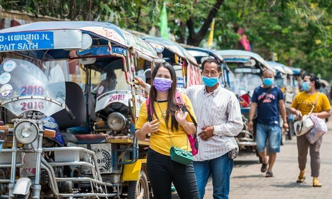 Người dân đeo khẩu trang trên đường phố Viêng Chăn, Lào hôm 23/3. Ảnh: Xinhua.