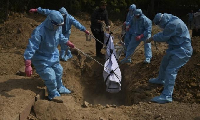 Thân nhân mặc đồ bảo hộ chôn cất bệnh nhân Covid-19 tại một nghĩa trang ở New Delhi, Ấn Độ, hôm 30/4. Ảnh: Reuters.