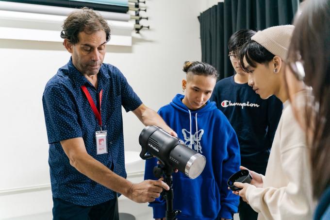Ông Mark Hamilton Gruchy hướng dẫn sinh viên thao tác dùng đèn studio trong lớp Nhiếp ảnh ở trường BUV. Ảnh: BUV.