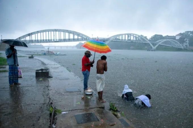 Thân nhân người chết vì lý do khác ngoài Covid-19 thực hiện nghi lễ ở sông Periyar trong cơn mưa lớn ở Kochi, bang Kerala, Ấn Độ, hôm 15/5. Ảnh: AP
