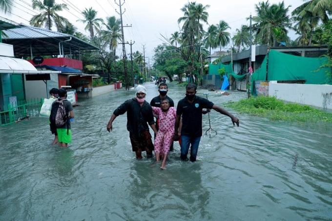 Nhân viên cứu hộ sơ tán một người dân qua con phố ngập lụt ở khu vực ven biển Kochi, tây nam Ấn Độ, sau trận mưa lớn do bão Tauktae hôm 14/5. Ảnh: AFP.