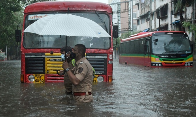 Cảnh sát giúp người điều khiển phương tiện giao thông công cộng băng qua đường ngập nước do bão Tauktae gây ra ở Mumbai, Ấn Độ, hôm 17/5. Ảnh: AFP.