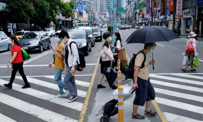 Người dân đeo khẩu trang đi lại trên đường phố Tân Đài Bắc, đảo Đài Loan, hôm 15/5. Ảnh: AFP.