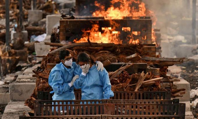 Gia đình một bệnh nhân tử vong vì Covid-19 tại nơi hỏa táng ở ngoại ô thành phố Bengaluru, Ấn Độ, hôm 13/5. Ảnh: Reuters.