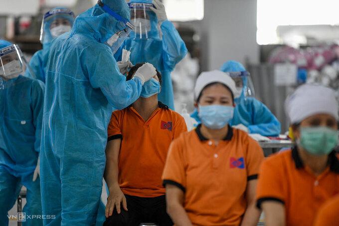 Nhân viến y tế lấy mẫu xét nghiệm tại KCN Quang Châu, huyện Việt Yên, tỉnh Bắc Giang, ngày 15/5. Ảnh: Giang Huy