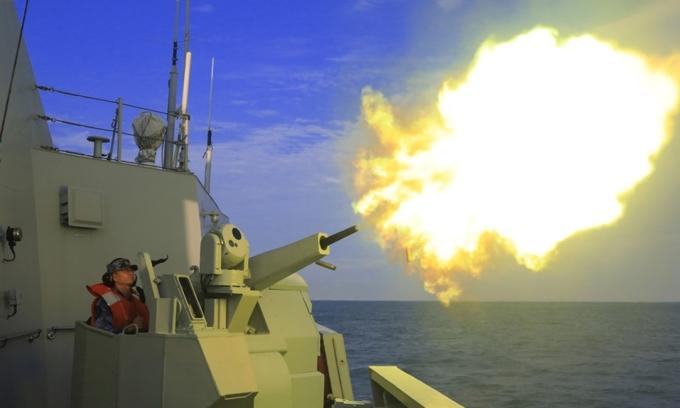 Một lính pháo binh trên tàu hộ vệ tên lửa Triều Châu khai hỏa vào máy bay mục tiêu trong cuộc huấn luyện trên biển ngày 29/4. Ảnh: Quân đội Trung Quốc.