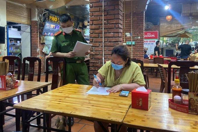 Công an phường Phúc Xá, Ba Đình, vận động người dân thực hiện yêu cầu tạm dừng kinh doanh quán bia để phòng dịch. Ảnh: Lê Khanh