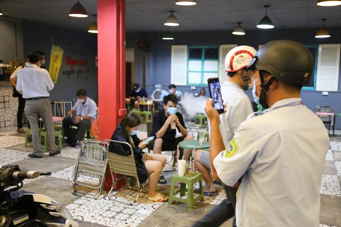 Nhân viên UBND phường 25 ghi hình quán cà phê vi phạm để làm căn cứ xử phạt. Ảnh: Đình Văn.