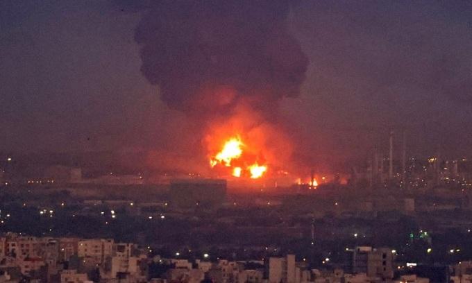 Khói và lửa vẫn bốc lên từ  đám cháy nhà máy lọc dầu Tondguyan sau khi trời tối. Ảnh: AFP.