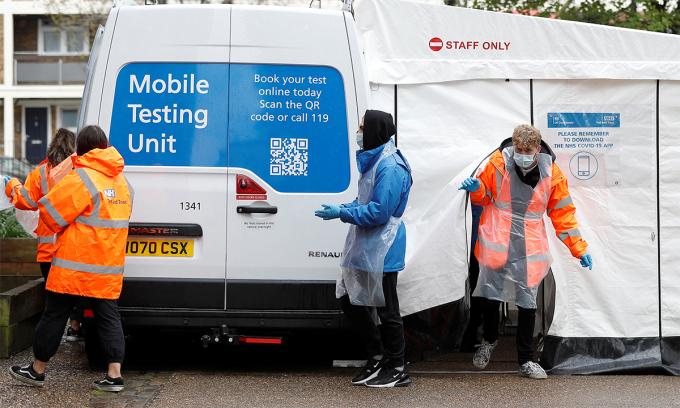 Nhân viên y tế Anh tại một điểm lấy mấu xét nghiệm Covid-19 lưu động ở London ngày 2/5. Ảnh: Reuters.
