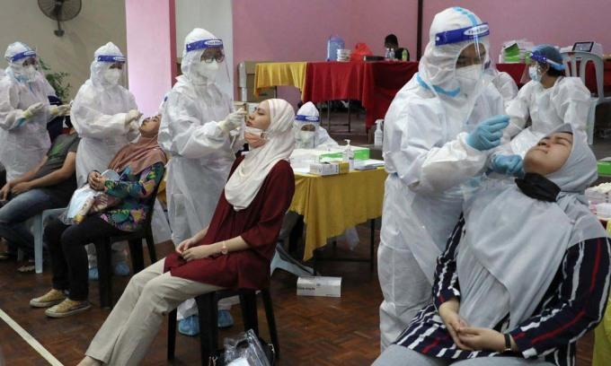 Nhân viên y tế lấy mẫu xét nghiệm nCoV cho người dân tại Cyberjaya, Malaysia, hôm 2/6. Ảnh: Reuters.