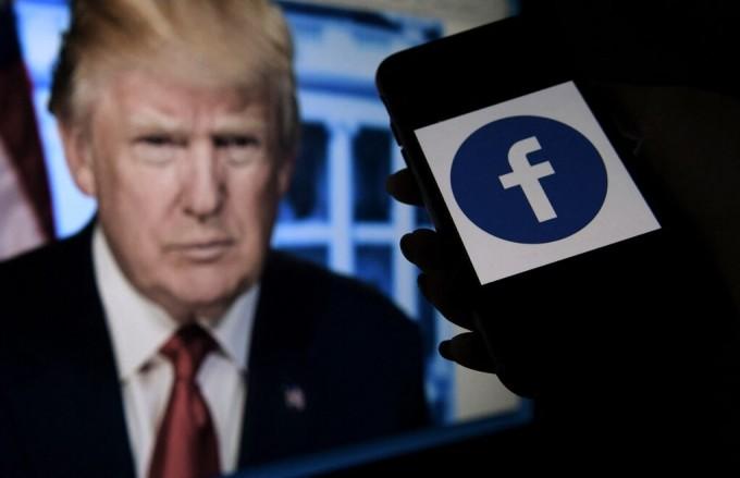 Điện thoại với hình logo Facebook được đặt cạnh ảnh chân dung Trump. Ảnh: AFP.