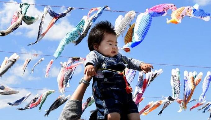 Người bố nâng em bé tại công viên ở ngoại ô Tokyo năm 2016. Ảnh: AFP.