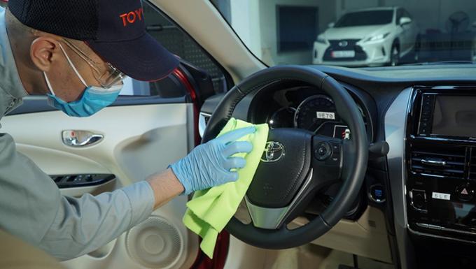 Nhân viên tại một đại lý Toyota chăm sóc xe cho khách hàng.