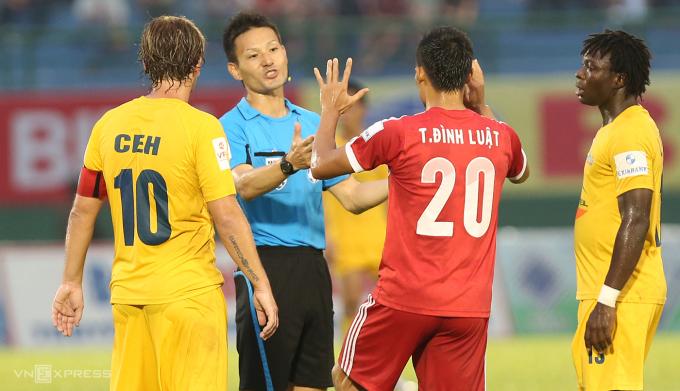 Trọng tài Sato xử lý một tình huống tranh chấp trong trận Bình Dương (đỏ) - Thanh Hoá ở V-League 2014. Ảnh: Đức Đồng.