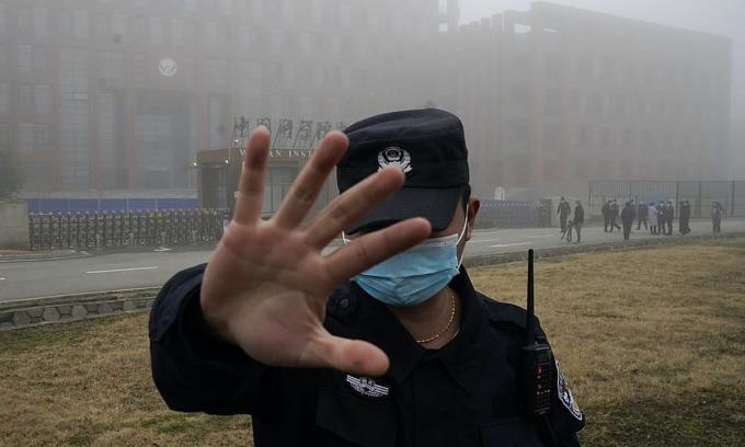Nhân viên bảo vệ dẫn các phóng viên rời Viện Virus Vũ Hán sau khi nhóm chuyên gia WHO đến thăm điều tra thực địa ở Vũ Hán ngày 3/2. Ảnh: AP.