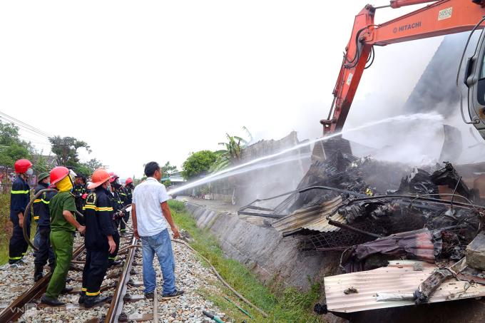 Trưa 12/6, cảnh sát dùng cần cẩu kéo sập nhà kho để khống chế ngọn lửa. Ảnh: Việt Anh