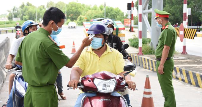 Cảnh sát kiểm tra thân nhiệt người đi đường khi vào địa phận tỉnh Tiền Giang. Ảnh: Nam An
