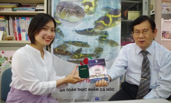 Vu Thuy Linh (trái), cầm chứng chỉ chế biến cá nóc, cạnh Shigeru Yamamoto, giáo sư dinh dưỡng quốc tế tại Đại học Jumonji, cầm video giới thiệu các biện pháp cần chú ý để đảm bảo an toàn khi chế biến cá nóc, ngày 26/5. Ảnh: Kyodo News.