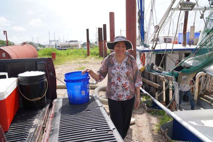 Phuong Thi Nguyen, một phụ nữ Việt Nam sinh sống ở Bayou La Batre, chất đá lên lạnh lên máy làm mát ở bến tàu hôm 14/6. Ảnh: AL.