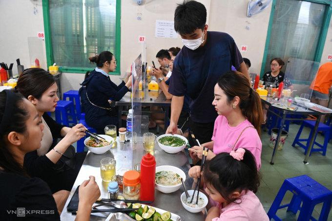 Người dân Hà Nội đi ăn phở trong ngày đầu một số dịch vụ được mở cửa trở lại, sáng 22/6. Ảnh: Giang Huy
