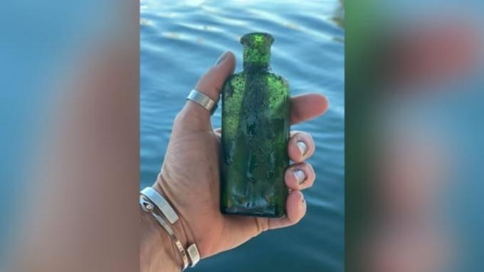 Chai thủy tinh màu xanh chứa thông điệp mà Dowker phát hiện dưới đáy sông Cheboygan hôm 18/6. Ảnh: Jennifer Dowker.