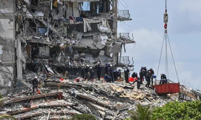 Nhân viên cứu hộ tìm kiếm đống đổ nát của tòa chung cư sập Champlain Towers khu Nam hôm 26/6. Ảnh: Washington Post.