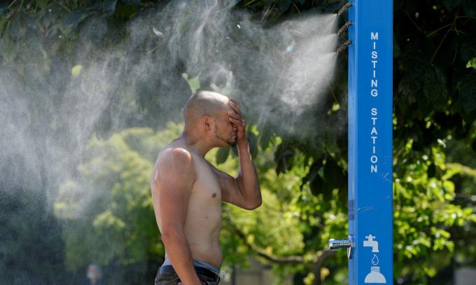 Một người đàn ông làm mát bằng trạm phun sương tại Vancouver, tỉnh British Columbia hôm 27/6. Ảnh: Reuters.