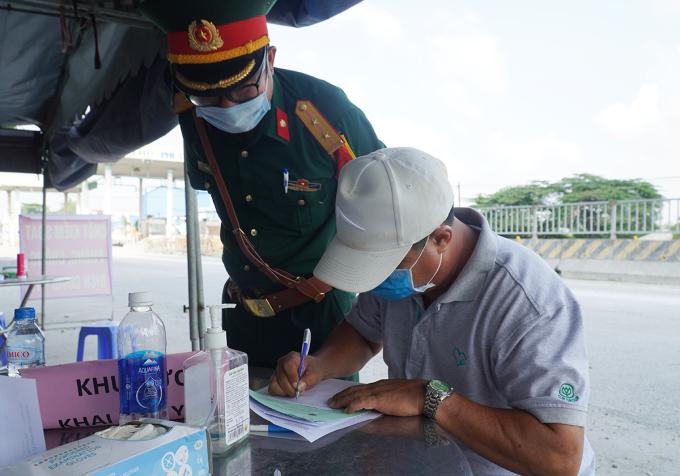 Cơ quan chức năng hướng dẫn tài xế khai báo y tế khi vào tỉnh Đồng Nai. Ảnh: Phước Tuấn