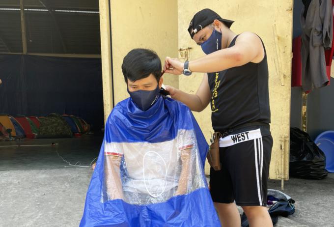 Công nhân Xí nghiệp lốp Radial cắt tóc cho đồng nghiệp trong khu lưu trú tạm. Ảnh: An Phương.