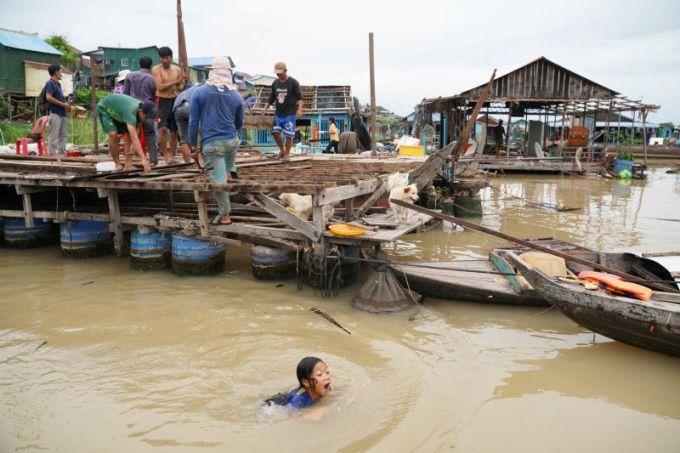 Người dân phá vỡ nhà nổi trên sông Tonle Sap sau khi được lệnh di dời của chính quyền hôm 12/6. Ảnh: Reuters.