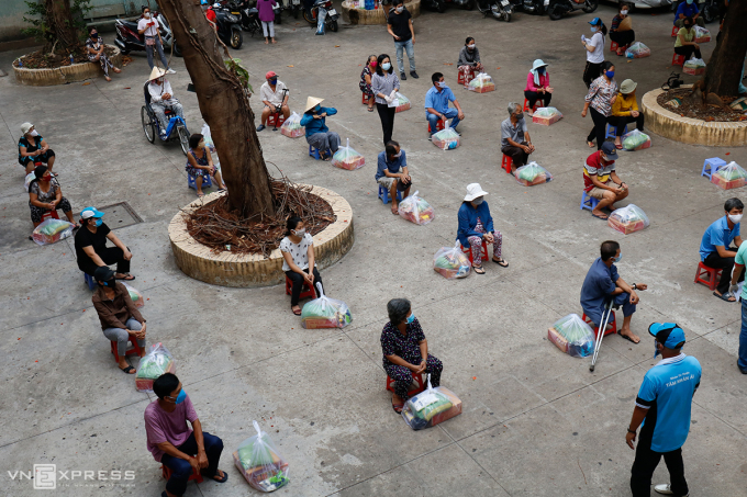 Người dân gặp khó khăn bởi dịch nhận quà của các nhà hảo tâm tại UBND phường 9, quận Phú Nhuận, hồi tháng 4/2021. Ảnh: Nguyệt Nhi.