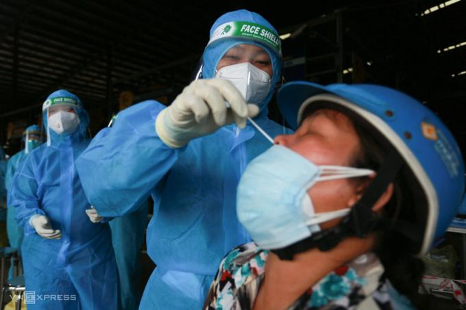 Nhân viên y tế lấy mẫu xét nghiệm tiểu thương chợ Bình Điền, quận 8 trưa 5/7. Ảnh: Hữu Khoa.