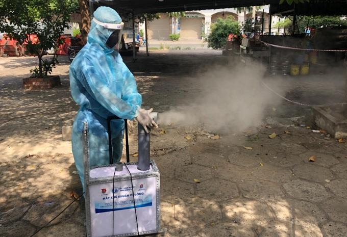 Một bạn trẻ phun xịt bằng máy khử khuẩn di động tại quận 8, sáng 6/7. Ảnh: Hạnh Hoa.