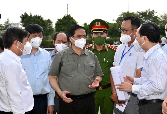 Thủ tướng nghe lực lượng chức năng báo cáo việc thực hiện Chỉ thị tại phường Tân Phú, TP Thủ Đức chiều 11/7. Ảnh: VGP