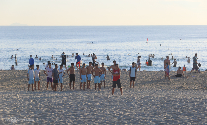 Một nhóm người tụ tập tại bãi biển không đeo khẩu trang, sáng 17/7. Ảnh: Đắc Thành.