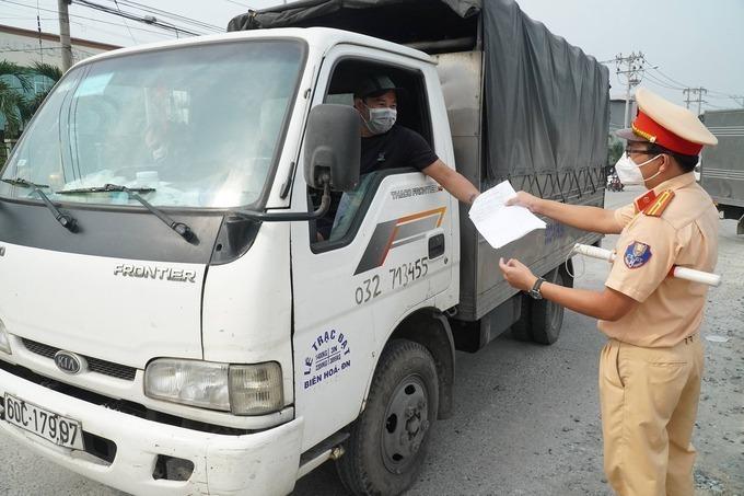 Cảnh sát giao thông kiểm tra giấy xác nhận xét nghiệm âm tính nCoV của tài xế tại chốt kiểm dịch trên quốc lộ 1K, TP Biên Hòa, sáng 5/7. Ảnh: Phước Tuấn