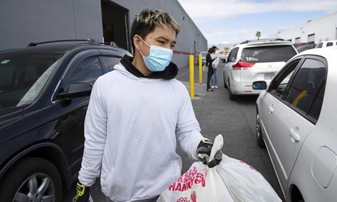Nam Tran mang túi đựng thực phẩm lên xe đỗ ở ngân hàng thực phẩm của Hội đồng Phát triển Cộng đồng châu Á tại Las Vegas hồi tháng 3. Ảnh: Steve Marcus.