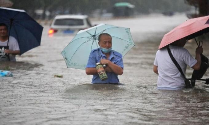 Người dân lội qua nước lũ ở Trịnh Châu.  Ảnh: Reuters.