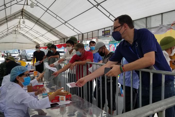 Người dân trong nước và khách nước ngoài làm thủ tục vào thành phố Hải Phòng tại chốt kiểm soát dịch Covid-19 liên ngành cuối đường cao tốc Hà Nội- Hải Phòng, quận Hải An. Ảnh: Giang Chinh